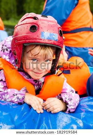 Happy little girl wearing helmet sitting in a rafting boat - stock photo