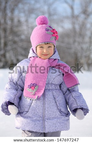 Happy little girl wearing in pink scarf and hat smiles next winter forest.