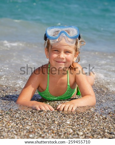 Happy little girl wearing snorkeling mask lying in the sea - stock photo