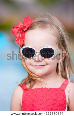 Happy little girl wearing sunglasses outdoors