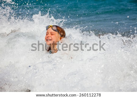 Happy little girl wearing swim goggles playing in the sea - stock photo