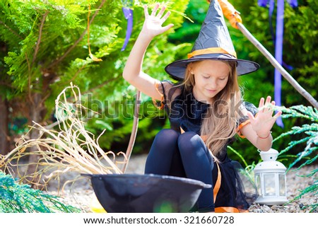 Happy little girl wearing witch costume on Halloween outdoors. Trick or treat.