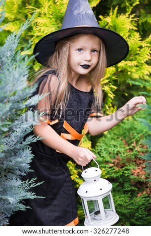 Happy little girl wearing witch costume on Halloween outdoors. Trick or treat. - stock photo
