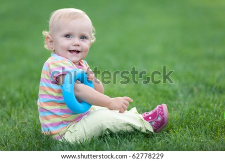 Happy little girl with a blue toy circle on her right hand is sitting on the grass