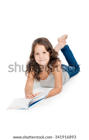 happy little girl with a book lying on the floor