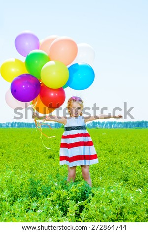 Happy little girl with a bunch of colorful balloons on a summer meadow. - stock photo