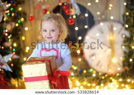 happy little girl, with a gift in hands, smiles and looks in the camera. Waiting for a holiday.