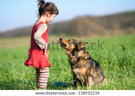 Happy little girl with and her dog looking at each other in the field - stock photo