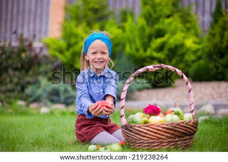 Happy little girl with autumn harvest of tomato in basket