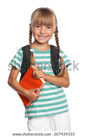 Happy little girl with backpack and books isolated on white background