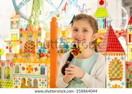 Happy little girl with beautiful eyes smiling at camera and holding lollipop in hands - stock photo