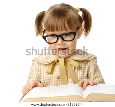 Happy little girl with big book wearing black glasses, back to school concept, isolated over white - stock photo
