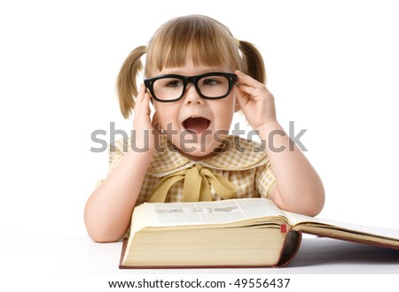Happy little girl with big book wearing black glasses, isolated over white - stock photo