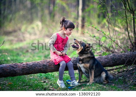 Happy little girl with big dog in the forest - stock photo