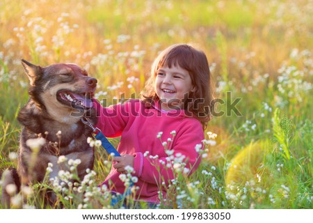 Happy little girl with big dog sitting in the lawn - stock photo