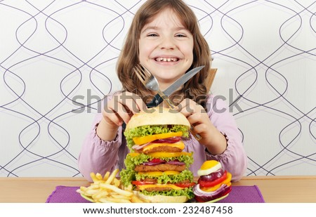 happy little girl with big hamburger - stock photo
