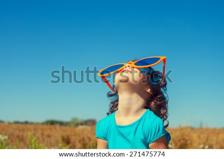 Happy little girl with big sunglasses looking at the sky - stock photo