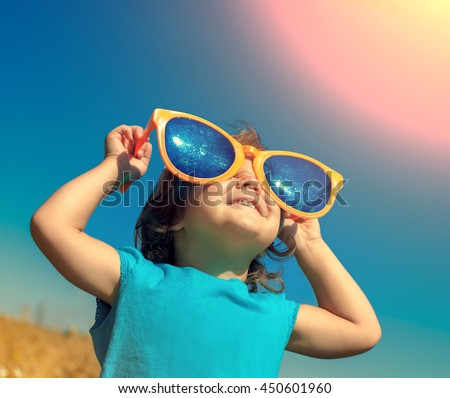 Happy little girl with big sunglasses walking in the meadow and looking at the sun