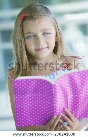 Happy little girl with book - stock photo