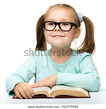 Happy little girl with book wearing black glasses, back to school concept, isolated over white - stock photo