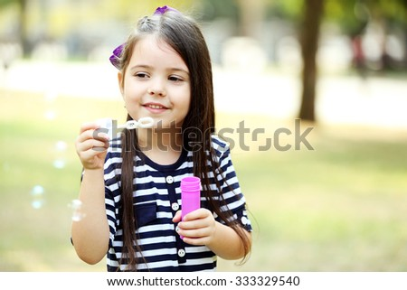 Happy little girl with bubbles in the park - stock photo