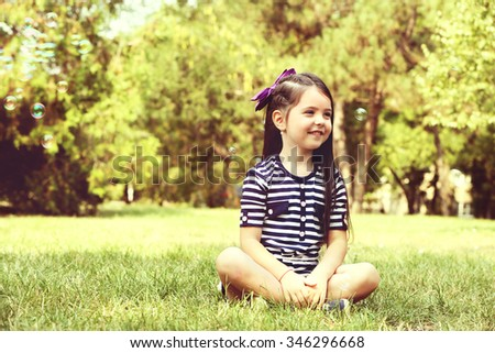 Happy little girl with bubbles on the green grass in the park - stock photo