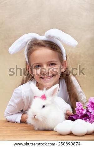 Happy little girl with bunny ears and her cute white rabbit preparing for easter - stock photo