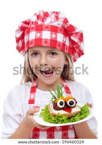 Happy little girl with chef hat and creative sandwich- isolated portrait - stock photo
