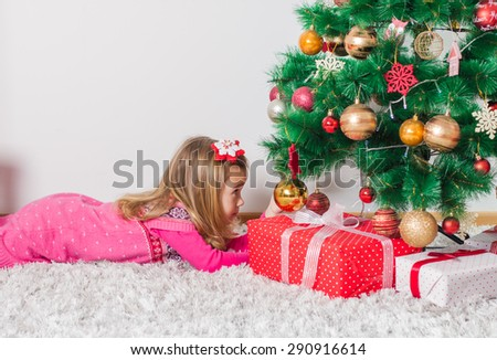 Happy Little Girl with Christmas Gift and Winter Tree with New Year decoration at home. - stock photo