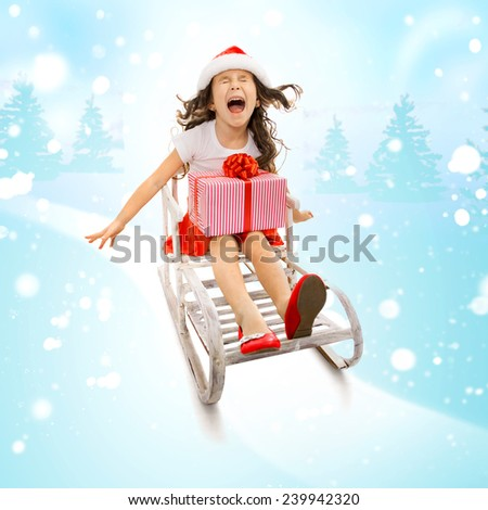 Happy little girl with Christmas gift box on a sled.  Holidays, christmas, new year, x-mas concept. - stock photo