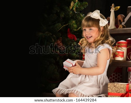 Happy little girl with Christmas gifts sitting near Christmas tree. Lots of copyspace - stock photo