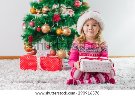 Happy Little Girl with Christmas Present and Winter Tree with New Year decoration at home. - stock photo