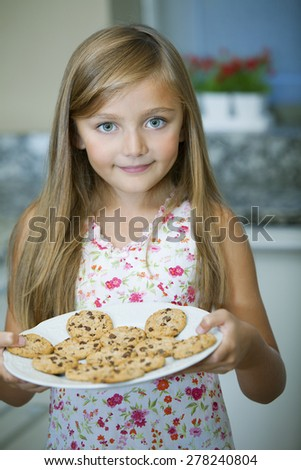 Happy little girl with cookies - stock photo