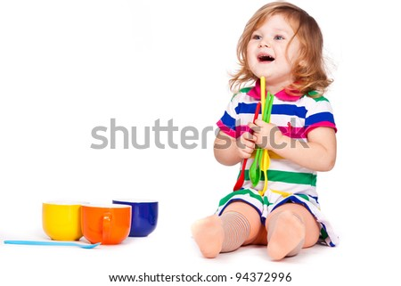 Happy little girl with cups and spoons - stock photo