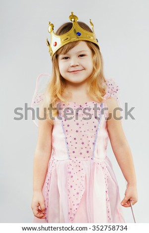 Happy little girl, with curly blond hair, wearing on pink dress, golden crown and fairy wings on her back, standing on white background, in studio, waist up - stock photo