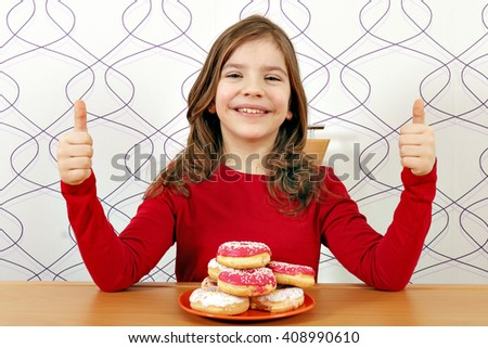 happy little girl with donuts and thumbs up - stock photo