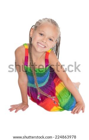 Happy little girl with dreadlocks sits on the floor. Girl six years. - stock photo
