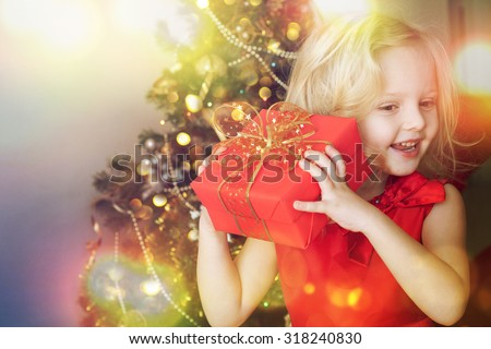 Happy little girl with gift - stock photo