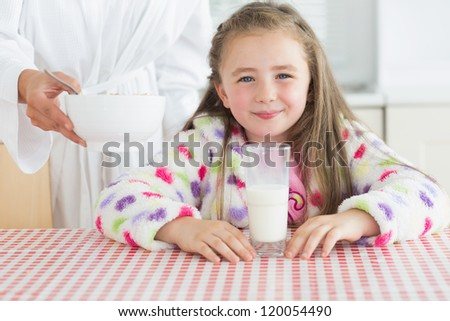 Happy little girl with glass of milk getting cereal from her mother at breakfast in kitchen - stock photo