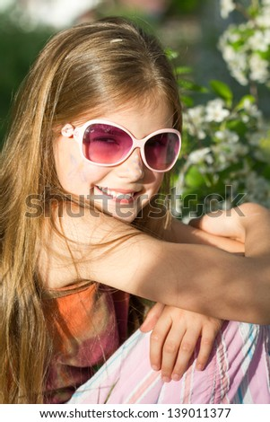 Happy little girl with glasses posing in the grass