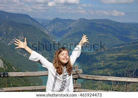 happy little girl with hands up on mountain