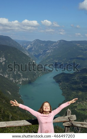 happy little girl with hands up on mountain enjoy in nature