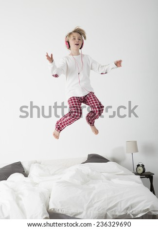 Happy Little Girl with Headphones jumping in bed - stock photo