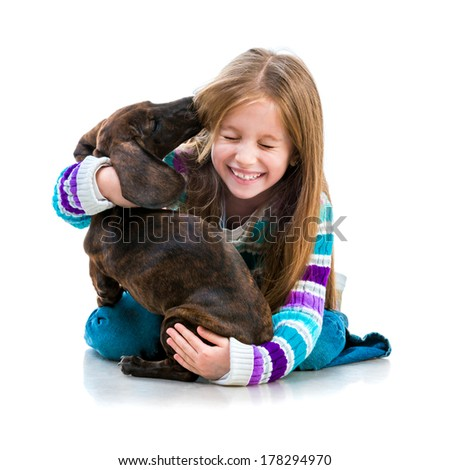 happy little girl with her �¢??�¢??dachshund in the studio on a white background - stock photo