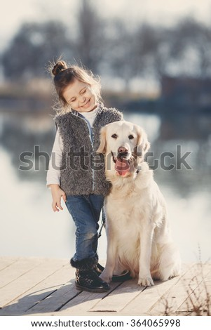 happy little girl with her dog golden retriever sitting on the bridge by the river. Cute little girl hugging golden retriever, smiling. The child with dogs. Puppies and child outdoor.