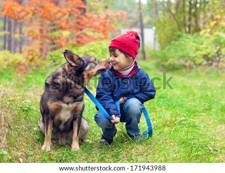 Happy little girl with her dog looking at each other in the forest in autumn - stock photo