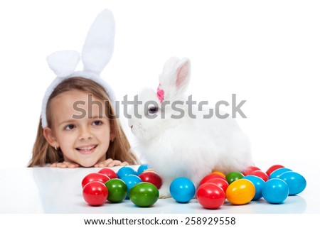 Happy little girl with her easter bunny - smiling and enjoying the magic, isolated - stock photo