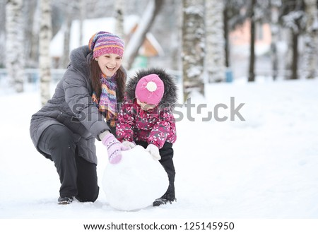 happy little girl with her mother rolled lumps of snow, make a snowman - stock photo