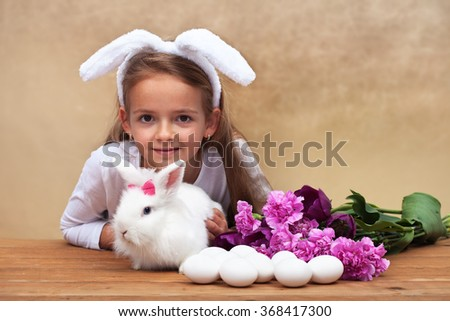Happy little girl with her spring rabbit and seasonal flowers - preparing for easter - stock photo