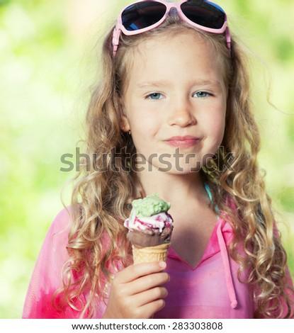 Happy little girl with ice cream outdoors - stock photo